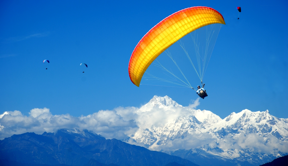 Mountain range view tandem paragliding flight